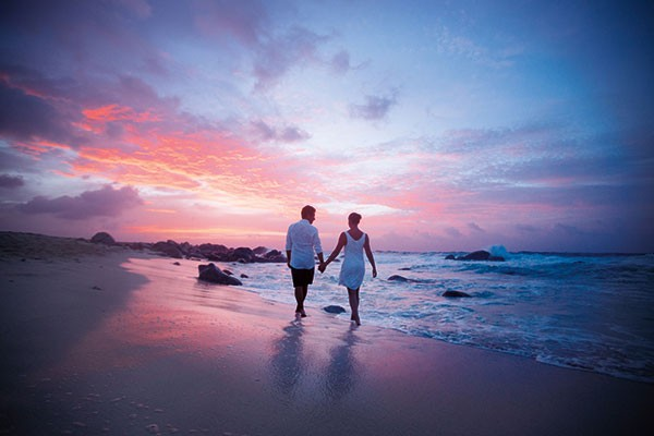 couple walking on the beach at sunset in Aruba