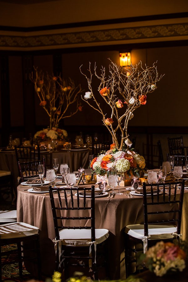 high wedding centerpiece with roses and hydrangeas and branches rising from center