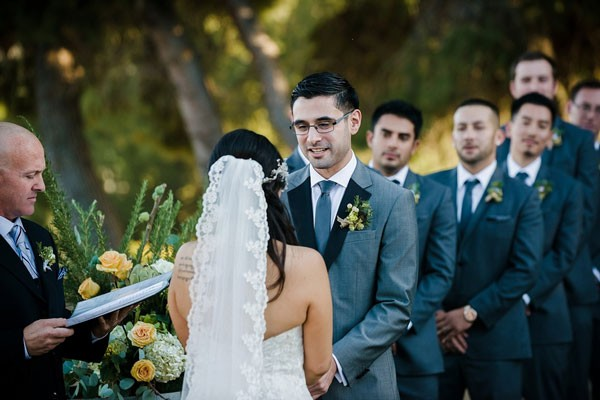 bride in scalloped lace veil and groom in gray suit exchanging vows with groomsmen looking on