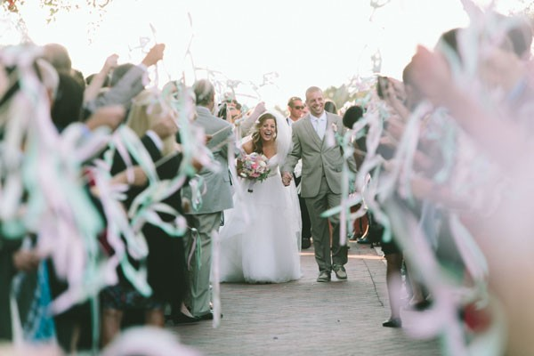 guests wave ribbon wands as bride and groom leave