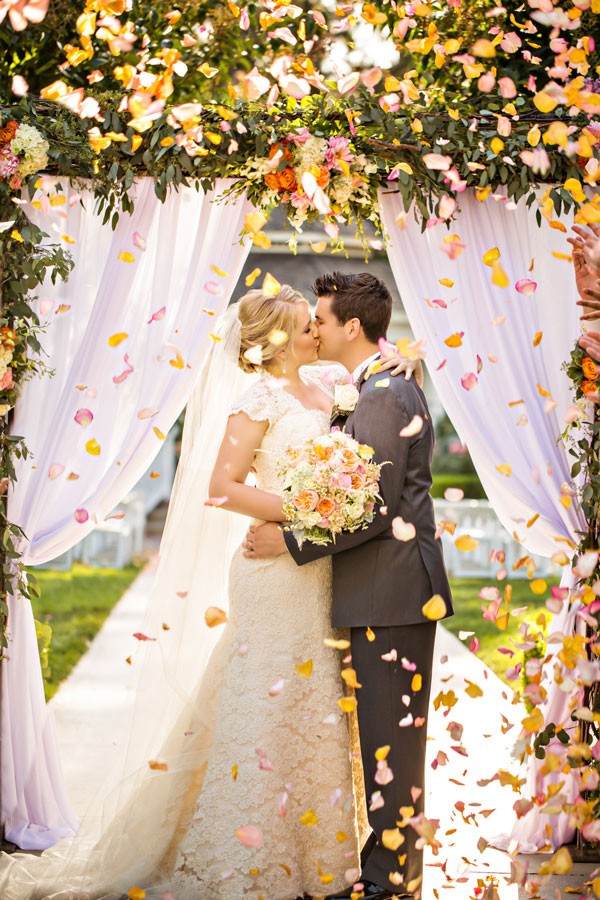 bride and groom kiss under arch with petals flying