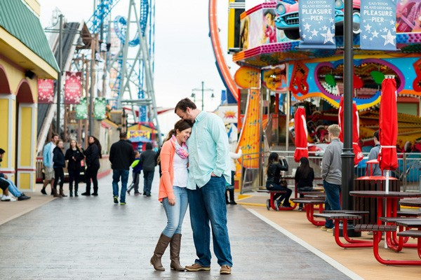 engaged couple standing on Pleasure Pier in Galveston, TX
