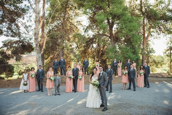 large wedding party in pink and gray standing by trees