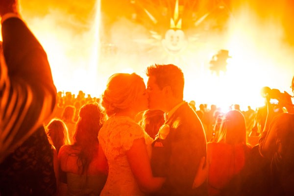 bride and groom kiss during Disney California's World of Color show