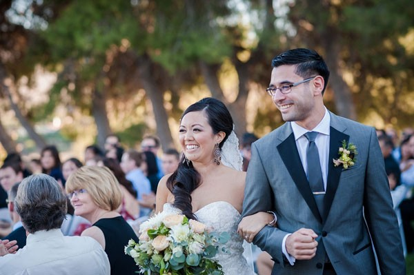 bride and groom smile as they walk back down the aisle at their vineyard ceremony