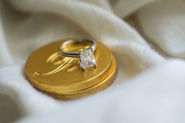 solitare diamond wedding ring on top of monogrammed gold wrapped chocolate coins