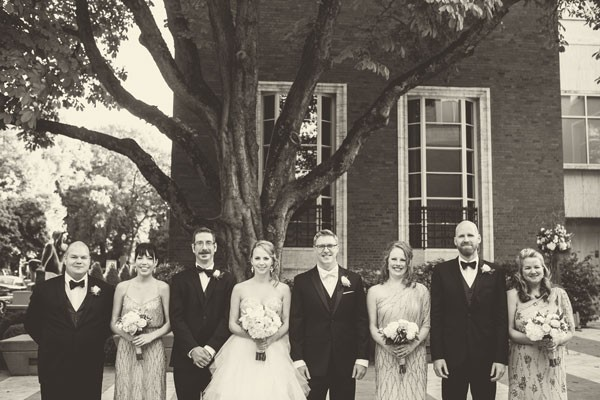 wedding party lines up in front of brick building and tree