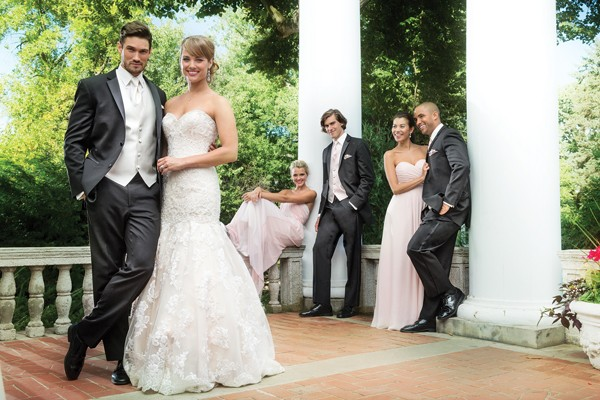 groomsmen in tuxedos and bridesmaids in light pink
