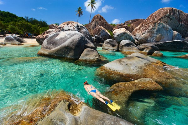 woman snorkeling by boulders in The Baths, British Virgin Islands