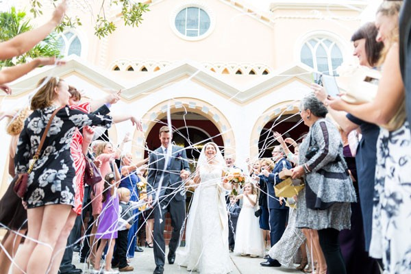 bride and groom leave church as streamers are tossed out in front of them