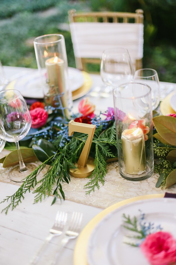 gold table number next to gold candles and wine glasses