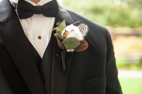 groom in black tuxedo with cotton and feather boutonniere