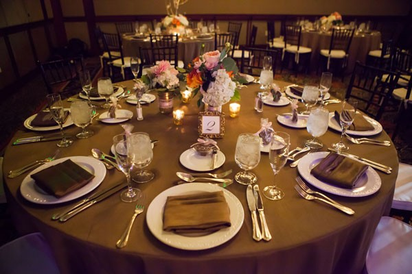 simple round reception tables with candles and low centerpiece, and dark taupe linens