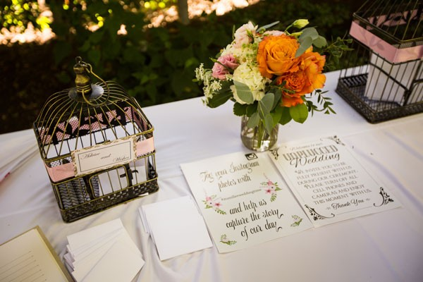 welcome table with small floral arrangement and Instagram sign