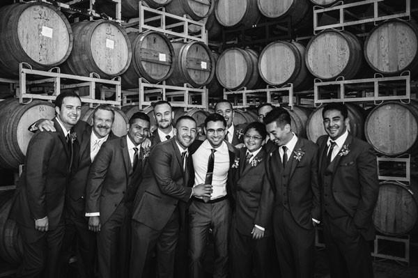 groomsmen standing in front of wine barrels