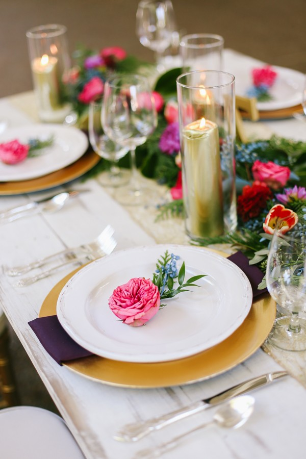 tablescap with gold plate chargers, lace runner, and gold candles with long swath of flowers and greenery