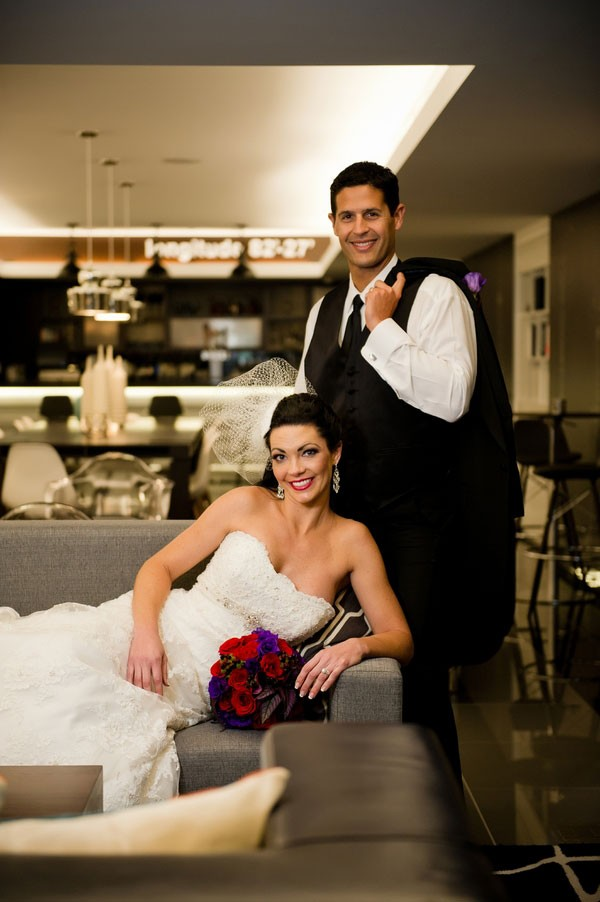 bride and groom pose in hotel wine bar after reception