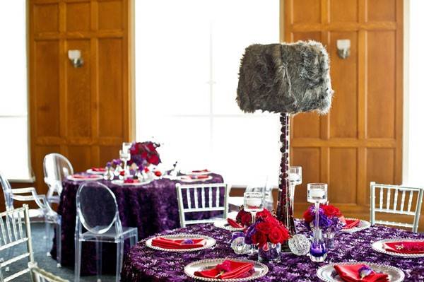 colorful reception decor with purple rosette linens, red napkins, and faux lamp filled with cherries
