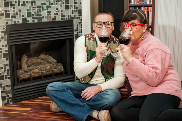 engagement photo with bride and groom wearing ugly sweaters and pretending to be geeky