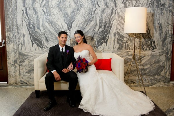 groom sits with bride in strapless wedding dress and red and purple bouquet