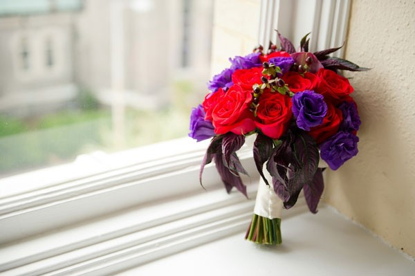 red and purple bridal bouquet with roses and lisianthus