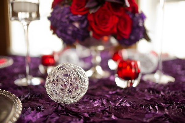 silver globe and red votives on top of purple rosette linens