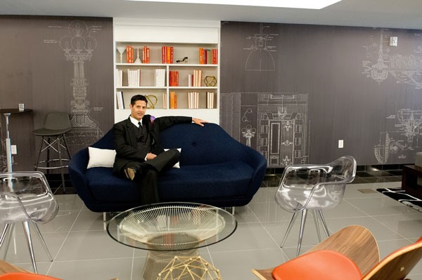 groom relaxes on sofa in modern hotel room