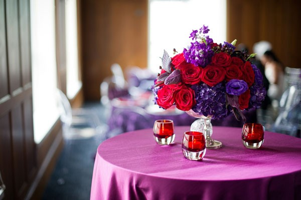 red rose and purple lisianthus on top of lilac tablecloth with red votives