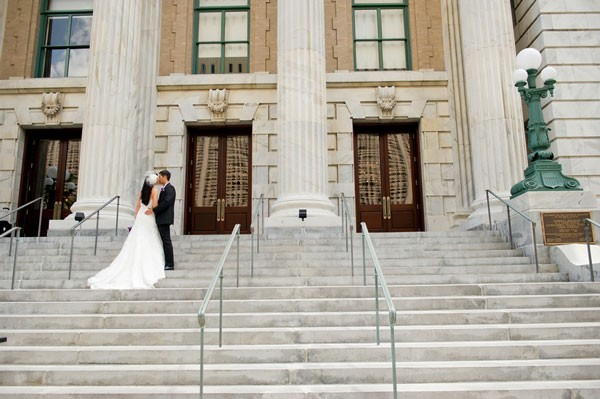 bride and groom kiss on exterior steps of historic hotel in Florida