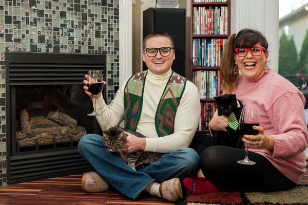 funny couple holding cats and drinking wine in humorous engagement session